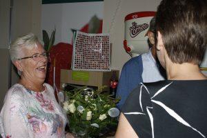 Mevrouw Van de Kreeke krijgt namens de directie van de Spar een boeket bloemen